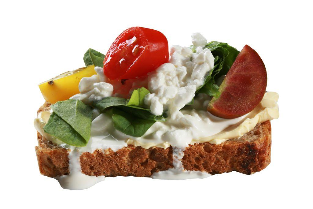 Kanapka z serkiem ziarnistym, szpinakiem, kolorowymi pomidorkami i szczypiorkiem